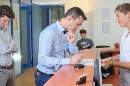 Photo pour Man filling out a form stood at reception desk - image libre de droit
