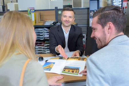 Photo pour Salesman showing brochure to couple - image libre de droit