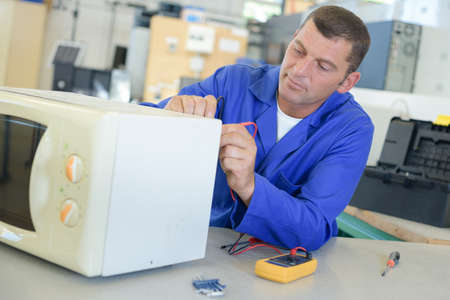 Photo pour technician fixing a microwave oven - image libre de droit
