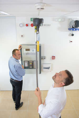 Photo pour Man reaching to test smoke detector with pole - image libre de droit