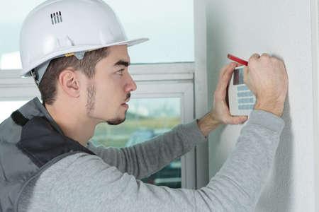 Photo pour worker installing alarm system in office - image libre de droit