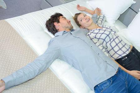 Foto de Couple testing new mattress - Imagen libre de derechos