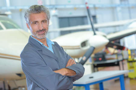 Photo pour Portrait of man in aircraft hangar - image libre de droit