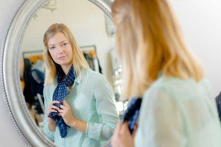 Photo pour Lady trying on scarf, looking at reflection in mirror - image libre de droit