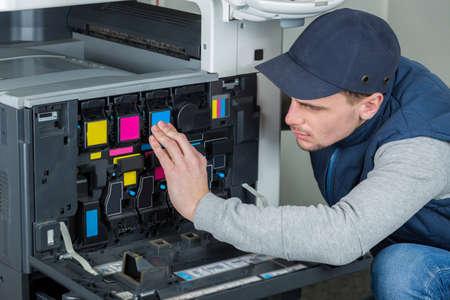 Photo pour Man checking ink cartridges in photocopier - image libre de droit
