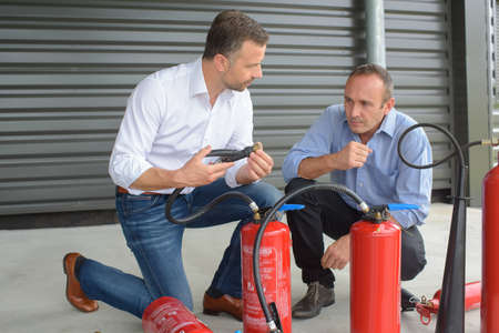 Photo pour Men examining fire extinguishers - image libre de droit