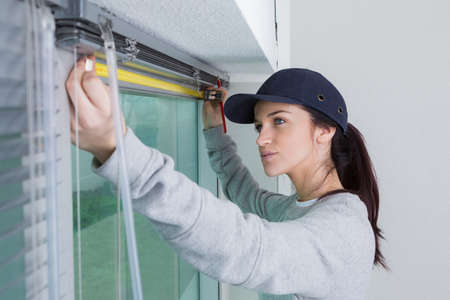 Photo pour Woman measuring for window blinds - image libre de droit