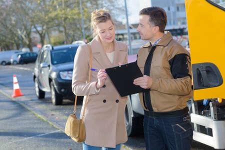 Photo pour tow truck driver talking with female client - image libre de droit