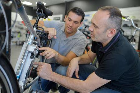 Photo pour mechanic repairing battery powered bicycle in his workshop - image libre de droit