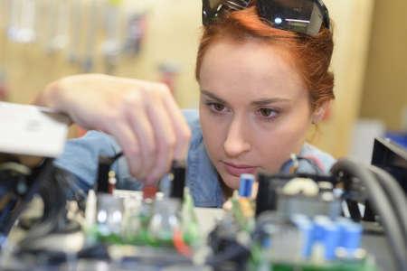 Foto de Woman looking closely at electronics board - Imagen libre de derechos