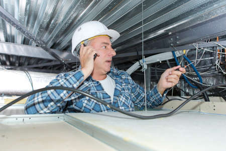Photo pour Electrician on the phone with client inside ceiling - image libre de droit