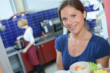 Photo pour Portrait of lady holding tray of food in commercial kitchen - image libre de droit