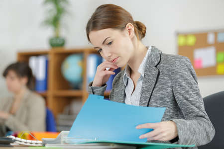 Photo pour attractive female office worker checks something in her folder - image libre de droit