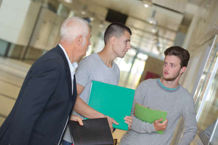 Photo pour male teacher walking in corridor with students - image libre de droit