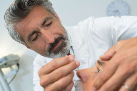 Foto de Doctor putting drops into patient's eye - Imagen libre de derechos