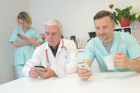 Photo pour Medical workers on a break, looking at their cellphones - image libre de droit