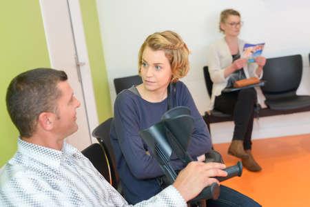Photo pour Couple in waiting room, man holding crutches - image libre de droit