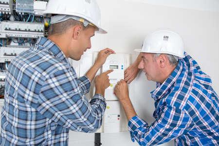 Photo pour engineer adjusting temperature on thermostat - image libre de droit