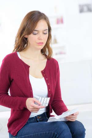 Foto de woman reading notice before talking pill - Imagen libre de derechos