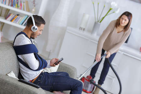 Photo for woman cleaning up while husband is relaxing on the sofa - Royalty Free Image