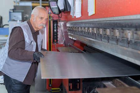 Photo pour man controlling hydraulic press machine for cutting steel - image libre de droit
