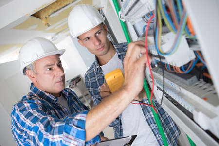Photo pour tutor instructing trainee electrician - image libre de droit