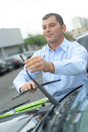 Photo pour man putting new wiper blade on his car - image libre de droit