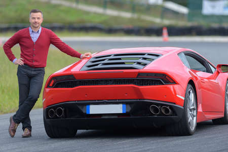Photo pour smiling man posing against red sport car on a circuit - image libre de droit