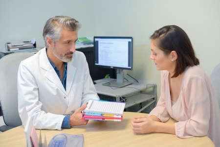 Photo pour happy patient and male doctor during consultation - image libre de droit