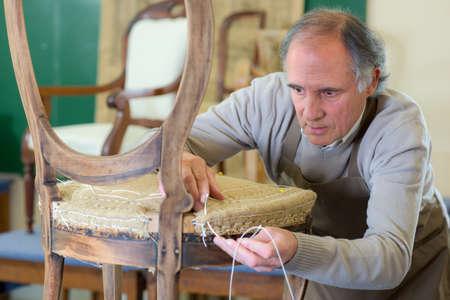 Photo pour Man uplholstering chair - image libre de droit