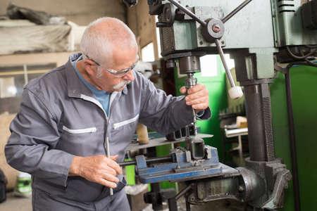 Foto de elderly worker watches processing of detail on milling machine - Imagen libre de derechos