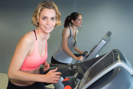 Photo pour blonde girl training on running machine in gym - image libre de droit