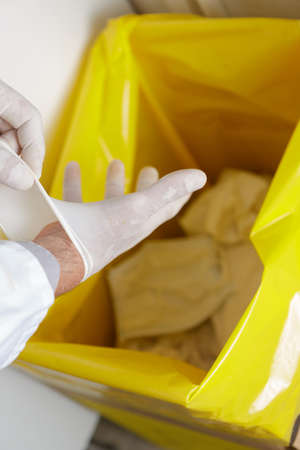 Photo for healthcare professional throwing away disposable latex gloves in trash - Royalty Free Image