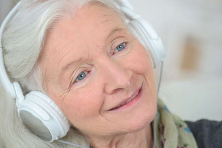 Photo pour friendly old lady listening music - image libre de droit