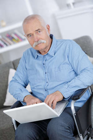 Photo pour disabled senior man sitting in wheelchair using laptop - image libre de droit