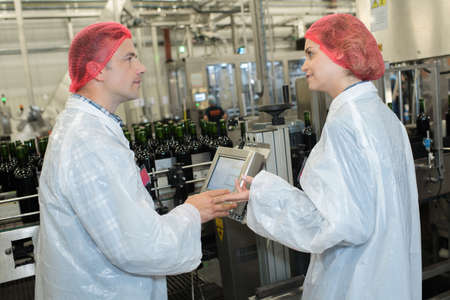 Photo pour workers in factory checking robotic line for bottling and packing - image libre de droit
