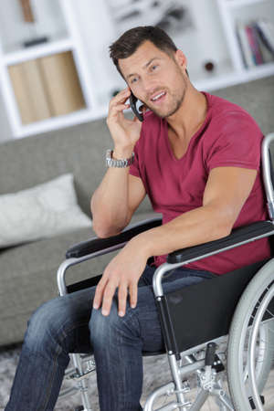 Photo pour handsome man in wheelchair talking on his phone and smiles - image libre de droit