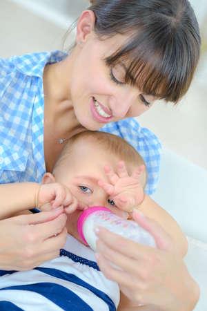 Photo pour Mother giving bottle to baby - image libre de droit