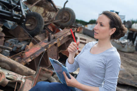 Photo pour young beautiful woman with clipboard working at landfill - image libre de droit