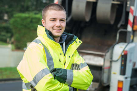 Photo pour young municipal garbage collector near garbage truck - image libre de droit