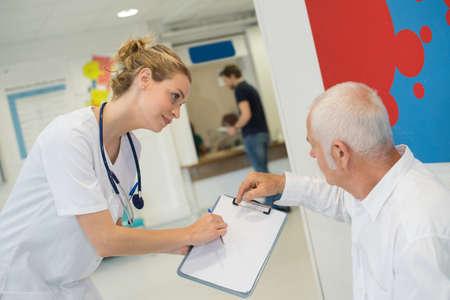 Foto de Medical worker showing paperwork to patient - Imagen libre de derechos