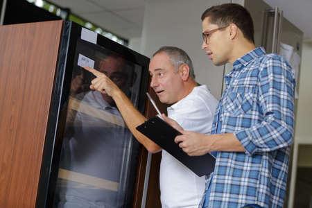 Photo pour Men looking at identification sticker on machine - image libre de droit