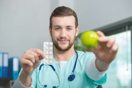 Photo pour smiling male nutritionist with an apple and pills - image libre de droit
