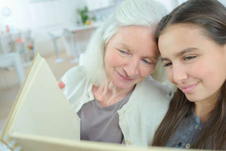 Photo pour woman and her granddaughter looking at an album - image libre de droit