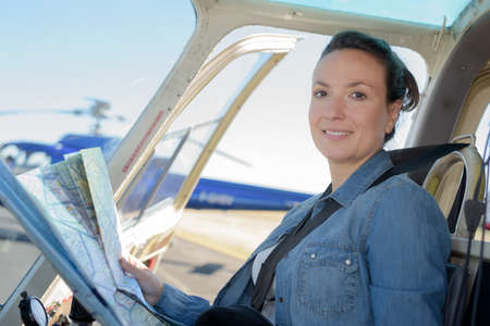 Photo pour young woman helicopter pilot reading map - image libre de droit