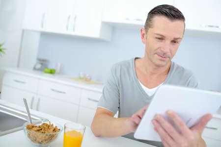Photo pour reading the online news during breakfast - image libre de droit