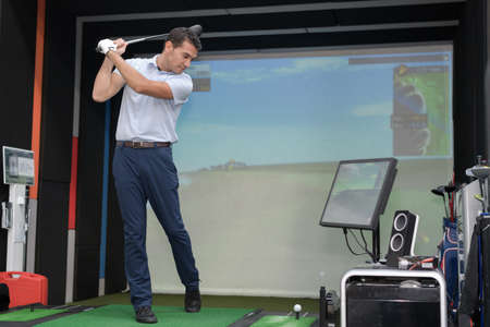 Photo pour Man practicing golf swing using simulator - image libre de droit