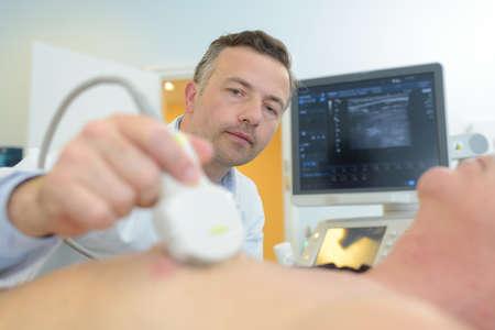 Photo pour Doctor performing ultrasound on chest area - image libre de droit