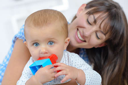 Photo pour Mother smiling at baby chewing toy - image libre de droit