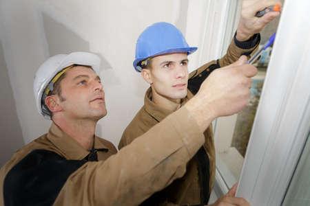 Photo pour Workmen fitting new window - image libre de droit